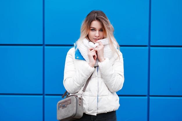 Молодая красивая модель девушка в модном вязаном шарфе и белой зимней куртке с кошельком позирует у синей стены