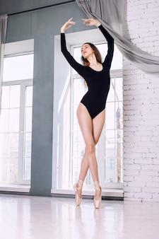 젊은 아름다운 모델 소녀는 훈련 바디수트와 pointe 신발에서 발레에 종사하고 있습니다
