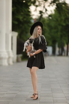 A young beautiful model girl in short summer dress joyfully walking on a city street with her small cute dog.