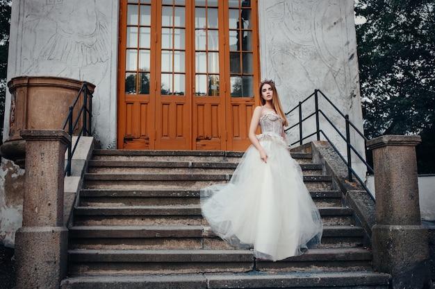 Молодая красивая модель позирует в длинном платье цвета слоновой кости в саду с короной на голове
