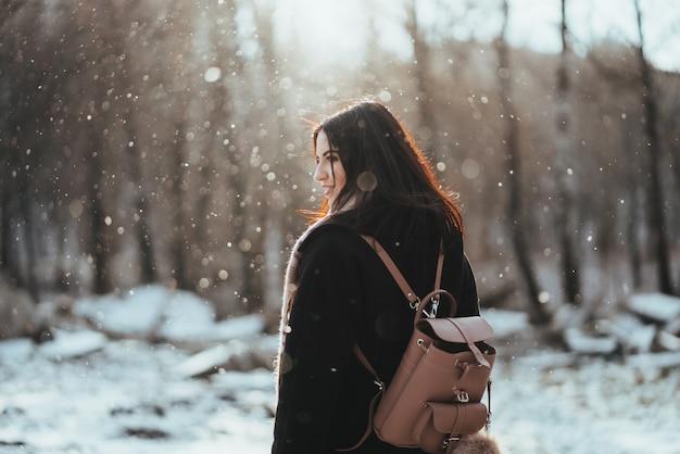 冬の森でポーズをとる若い美しいモデル。スタイリッシュなファッションの肖像画