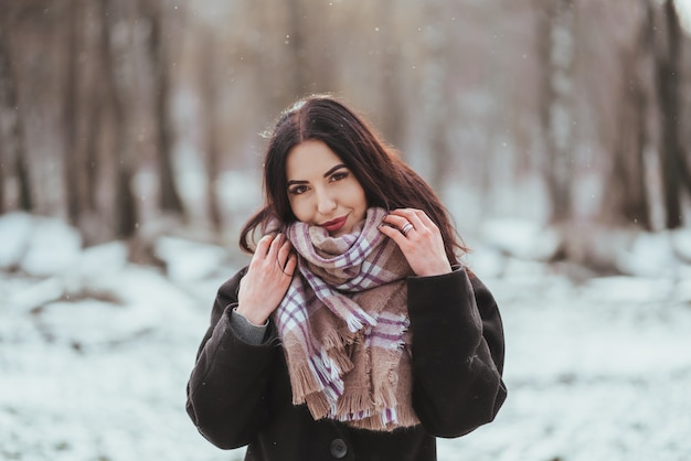 Young beautiful model posing in winter forest.