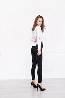 검은 색 청바지와 흰색 셔츠에 자연스러운 화장과 아름다운 머리를 한 젊은 아름다운 모델