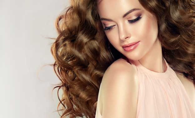 Young, beautiful model with wavy, dense and lush hairstyle, attractive and tender smile on her lips.