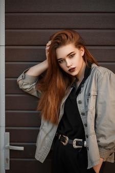 세련된 재킷과 검은 색 폴로에서 젊은 아름다운 모델 여자는 거리의 게이트 근처에 포즈
