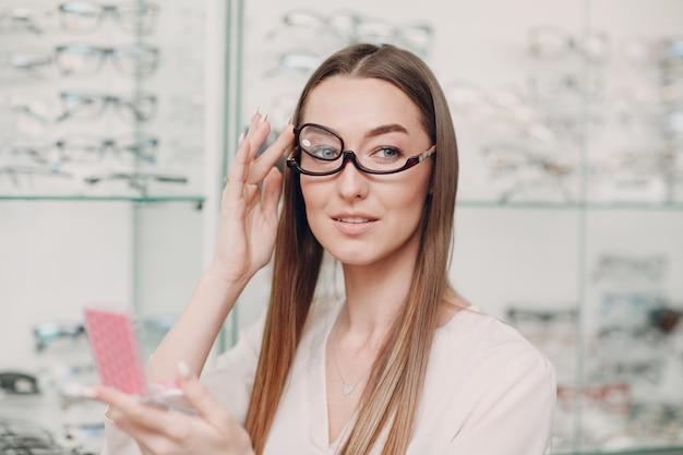 Молодая красивая модельная женщина в очках для макияжа в оптике. улыбающаяся женщина в очках для макияжа в оптическом магазине