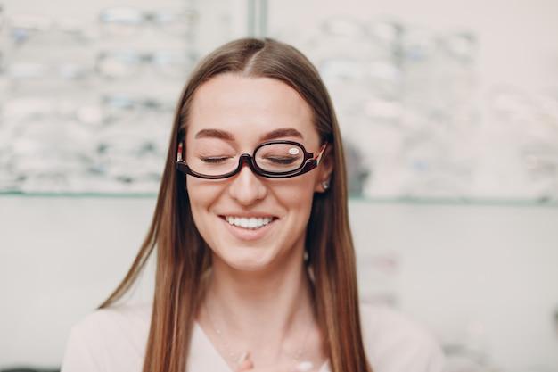 Молодая красивая модельная женщина в очках для макияжа в оптике улыбается женщина в очках для макияжа в оптическом магазине
