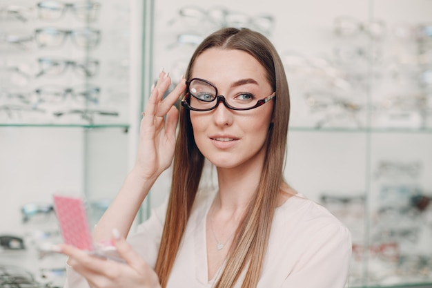 Young beautiful model woman with glasses for makeup in optician. smiling woman in eye glasses for make up in optical shop