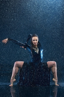 The young beautiful modern dancer dancing under water drops