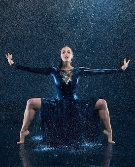Young beautiful modern dancer dancing under water drops