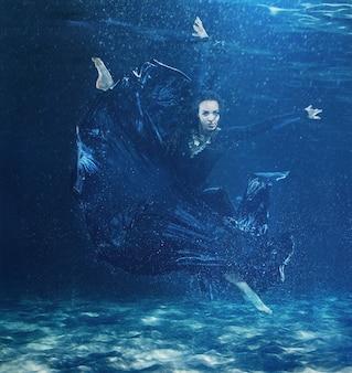 The young beautiful modern dancer in long dress dancing under water drops in blue aqua