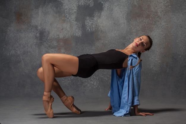회색 배경에 포즈 블루 셔츠에 젊은 아름 다운 현대적인 스타일 댄서
