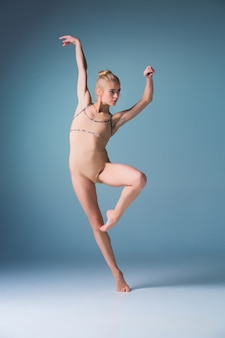 スタジオの背景にジャンプする若い美しいモダンなスタイルのダンサー