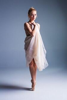 スタジオの背景にポーズをとる若い美しいモダンなスタイルのダンサー