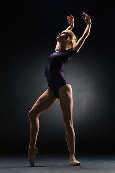 スタジオの暗い背景でポーズをとる若い美しいモダンなスタイルのダンサー
