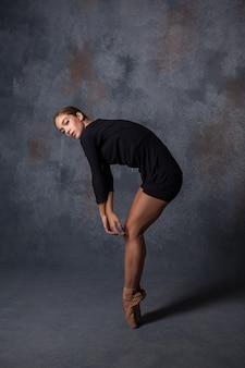 회색 배경에 포즈 젊은 아름 다운 현대적인 스타일 댄서