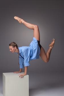 スタジオの灰色の背景に白い立方体でポーズをとる若い美しいモダンなスタイルのダンサー 無料写真
