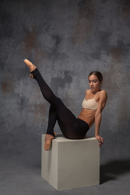 Young beautiful modern style dancer posing on white cube on gray background
