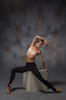 The young beautiful modern style dancer posing on white cube on a studio gray background