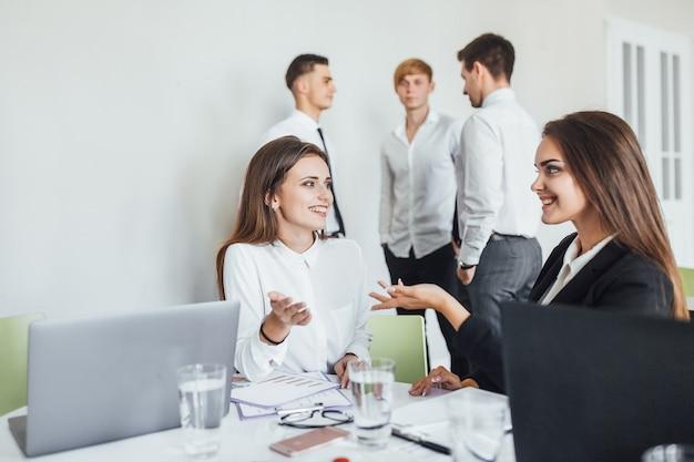 젊고 아름다운 현대 여성 동료들이 사무실에서 서로 의사소통하고 미소를 짓는다
