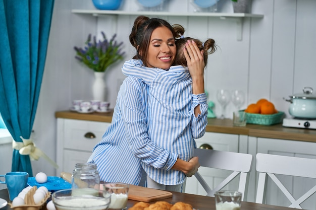 Young beautiful mom hugs her little daughter at home in the kitchen