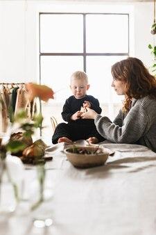 自宅の居心地の良いキッチンで一緒に時間を過ごす彼女の小さなハンサムな息子と夢のように遊んでいるニットセーターの赤い髪の若い美しいお母さん