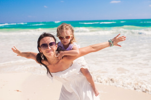 Young beautiful mother and adorable little daughter spread her arms like a bird on white beach