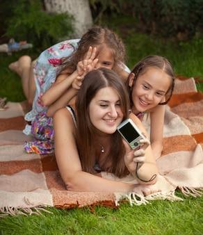 Молодая красивая мать и дочери фотографируются на пикнике
