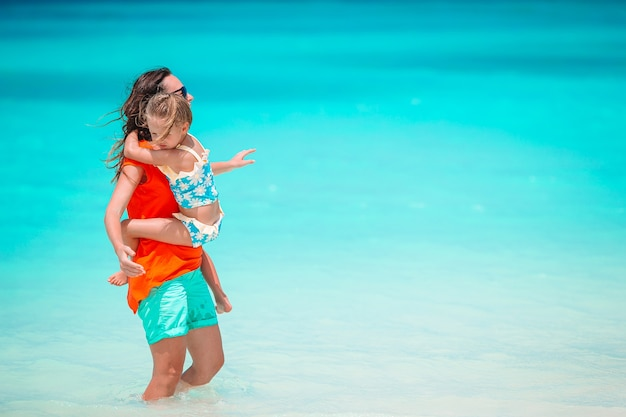 若い美しい母親と彼女の愛らしい小さな娘は熱帯のビーチで楽しんでいます