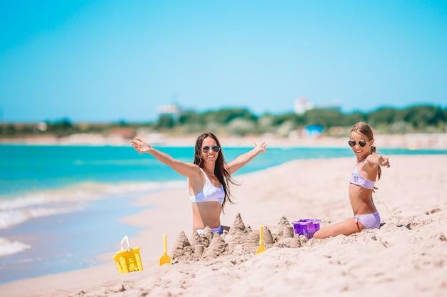 若い美しい母親と彼女の愛らしい小さな娘がビーチで楽しんで