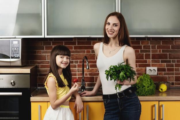 Молодая красивая мать и ее милая дочь стоя на кухне