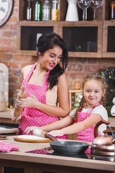 若い美しい母親と彼女の小さな娘が一緒にキッチンで料理
