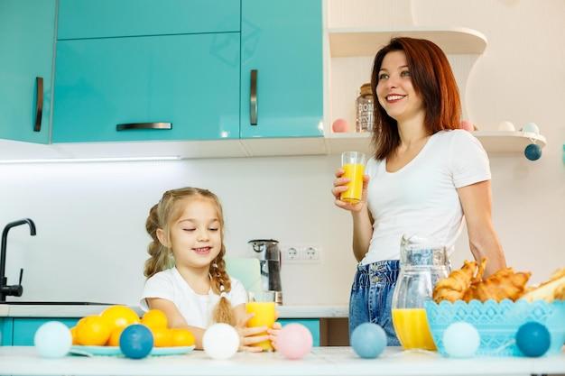 Молодая красивая мать и ее маленькая дочь, играя на кухне во время завтрака дома.
