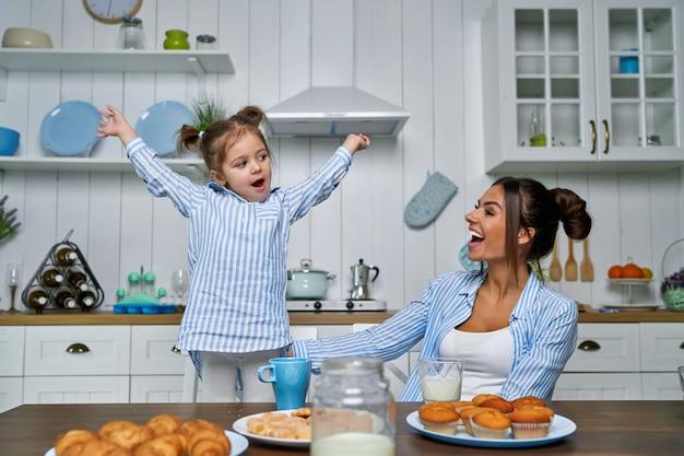 若い美しい母親と彼女の小さな娘は、自宅で朝食時にキッチンで遊んでいます。