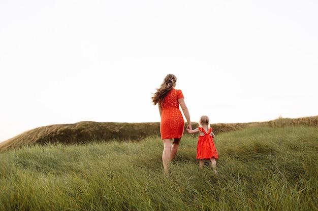 아름 다운 젊은 어머니와 여름 날 휴가에 자연을 걷는 작은 딸
