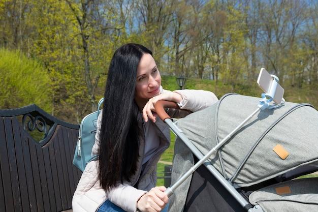 若い美しい母親、ベビーカーにかわいい赤ちゃんを持つ黒髪の女性は、電話から自撮りをします。