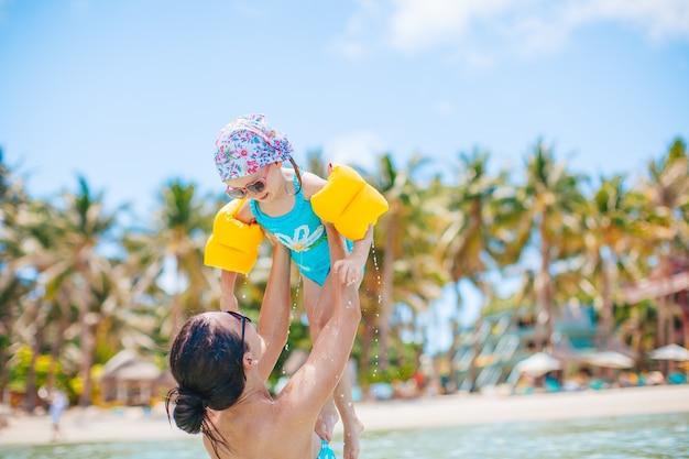 熱帯のビーチでの休暇で娘と楽しんでいる若い美しい母親