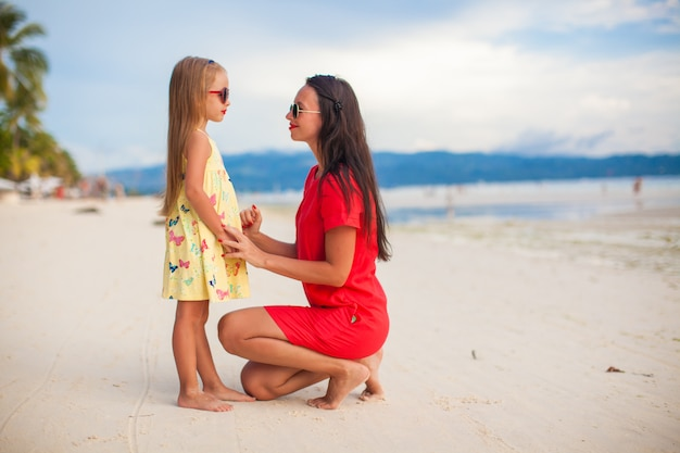 Young beautiful mother and her adorable daughter at sunset