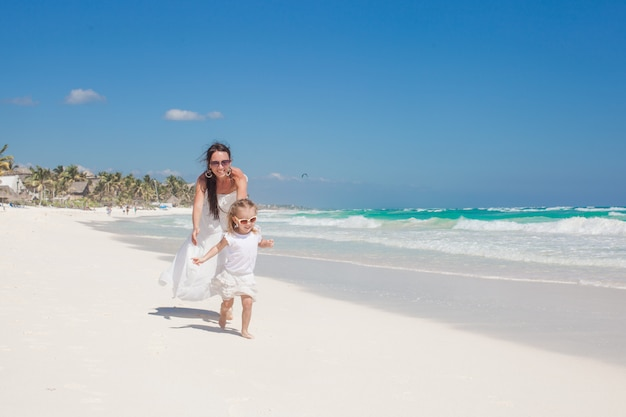 Young beautiful mother and her adorable little daughter running along the sea