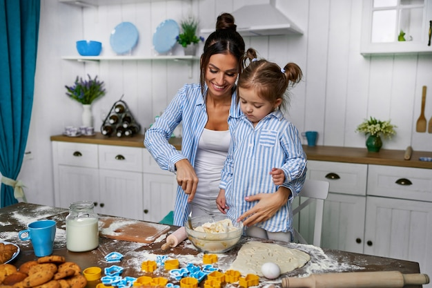 A young beautiful mother and her cute daughter stands in the kitchen at the table
