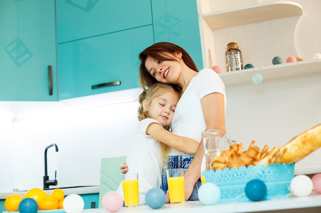 Young beautiful mother and her little daughter playing in the kitchen during breakfast at home.