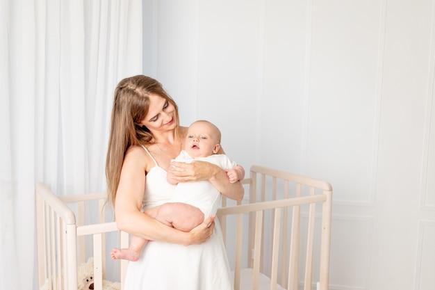 6 개월 그녀의 딸을 잡고 침대 옆에 보육 서에서 그녀를 포옹하는 젊은 아름다운 어머니