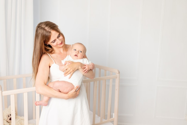 Young beautiful mother holding her daughter 6 months, hugging her in the nursery standing by the crib, mother's day, place for text