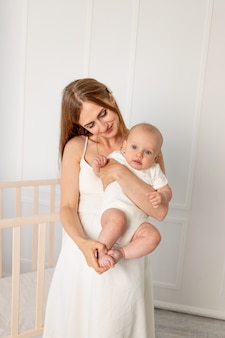 Young beautiful mother holding her daughter 6 months in the nursery, mother's day