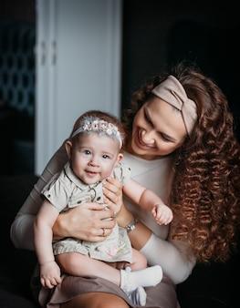 젊은 아름 다운 어머니는 그녀의 팔에 그녀의 아기 딸을 보유 하 고 그녀를 본다