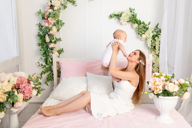 Young beautiful mother holds her daughter a girl of 6 months in her arms lifting her up on a white bed, mother's day, place for text