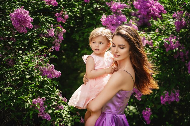若い美しい母親が腕の中で彼女の小さな娘を保持しています。母の日のコンセプトです。コピースペース