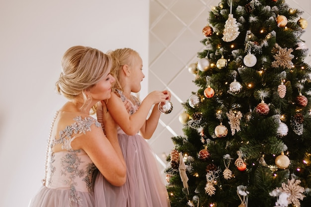 Young beautiful mother holds a little daughter who decorates a christmas tree