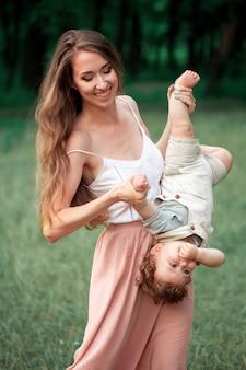 緑の芝生に対して彼女の小さな幼児の息子を抱いて若い美しい母親。夏の晴れた日に彼女の男の子と幸せな女。牧草地の上を歩く家族。