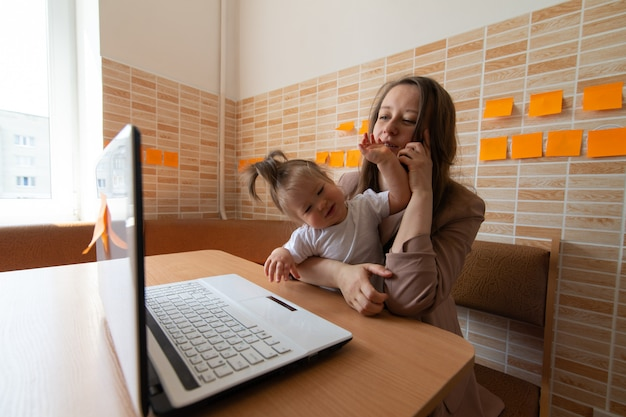 Young beautiful mother is trying to work remotely. her little daughter is bothering her.